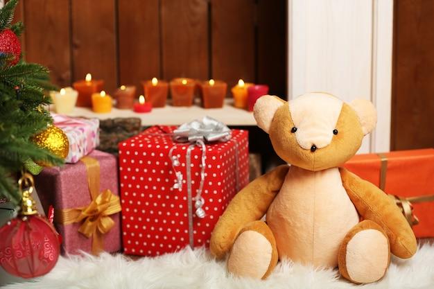 Urso de pelúcia com presentes de natal no quarto