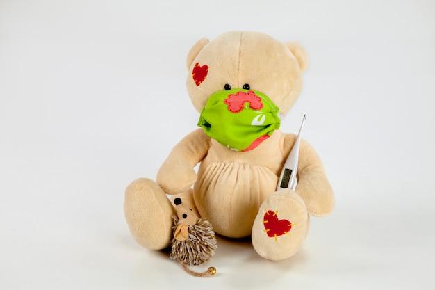 Urso de pelúcia com termômetro, máscara cirúrgica e rato de estimação