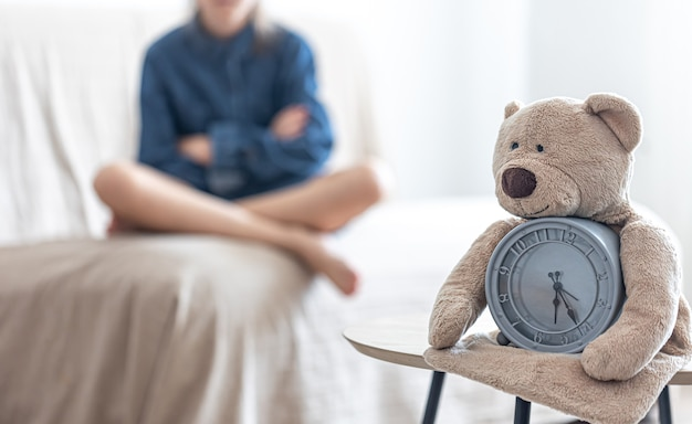 Urso de pelúcia com um despertador em um fundo desfocado do quarto de uma menina.