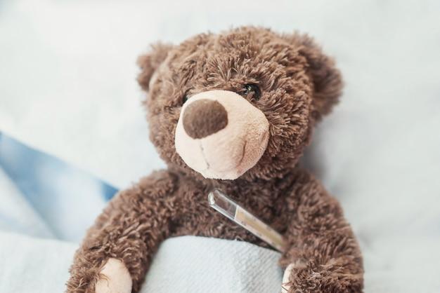Urso de pelúcia com um termômetro em uma cena azul