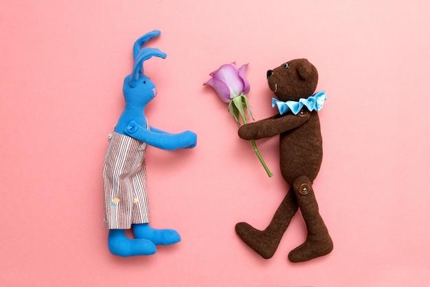 Urso de pelúcia dá uma flor para o coelho