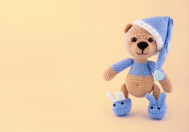 Urso de pelúcia de malha no boné e chinelos em fundo amarelo suave