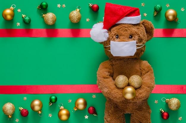 Urso de pelúcia de papai noel com máscara em verde turva com ornamentos.