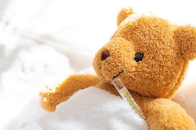 Urso de pelúcia deitado doente na cama com termômetro e gesso.