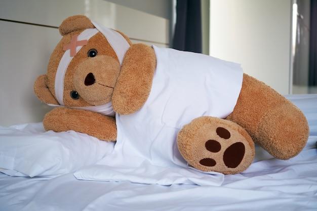 Urso de pelúcia deitado doente na cama com uma faixa de cabeça e um pano coberto