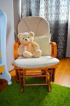 Urso de pelúcia em cadeira de balanço no interior do quarto das crianças