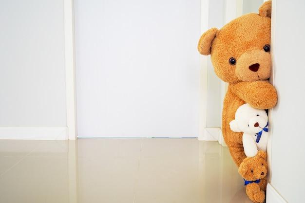 Urso de pelúcia em pé atrás da parede