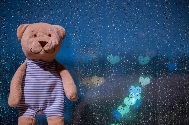 Urso de pelúcia em pé na janela quando chove com luzes coloridas do bokeh da forma do amor.