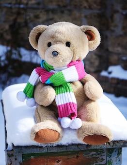 Urso de pelúcia em um lenço fica