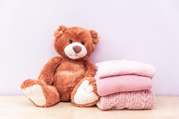 Urso de pelúcia fica perto de uma pilha de roupas femininas de inverno ou outono.