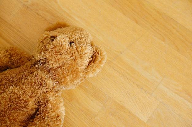 Urso de pelúcia fofo marrom no chão de madeira