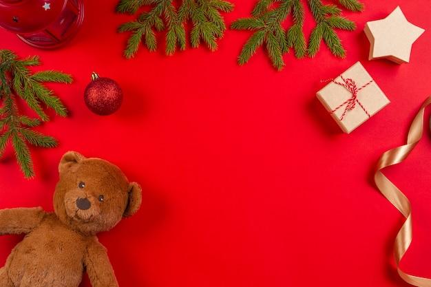 Urso de pelúcia, galhos de árvores de abeto, decorações de natal e caixa de presente em fundo vermelho