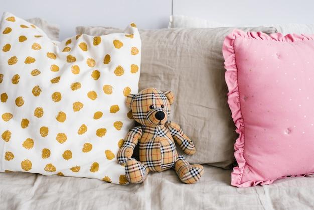 Urso de pelúcia infantil em uma gaiola na cama entre os travesseiros coloridos