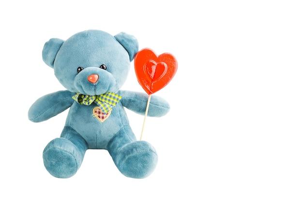 Urso de pelúcia macio turquesa com coração de pirulito vermelho em uma vara em um fundo branco, isolado. amor, um presente para uma garota, uma declaração de amor, dia dos namorados. copie o espaço