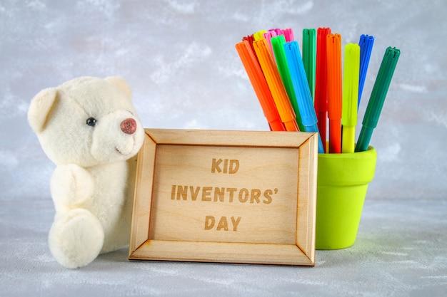 Urso de pelúcia, marcadores, placa sobre um fundo cinza. texto - kid inventors 'day.