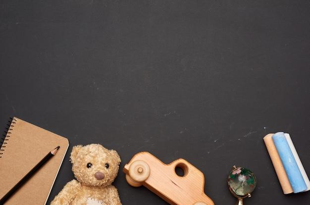 Urso de pelúcia marrom, carrinho de brinquedo de madeira e globo de vidro no quadro de giz preto