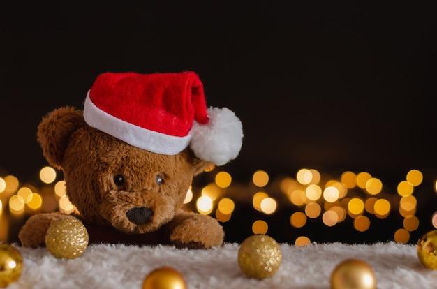 Urso de pelúcia marrom com chapéu de papai noel com enfeites de natal e fundo de luzes.