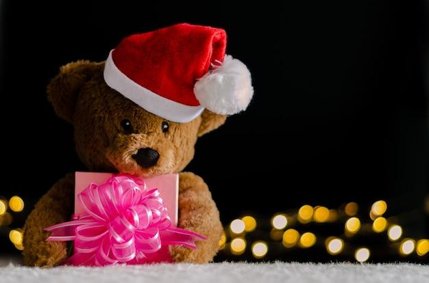 Urso de pelúcia marrom com chapéu de papai noel, segurando o foco parcial da caixa de presente de natal.