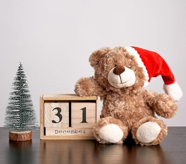 Urso de pelúcia marrom com chapéu vermelho, calendário de mesa de madeira com a data 31 de dezembro