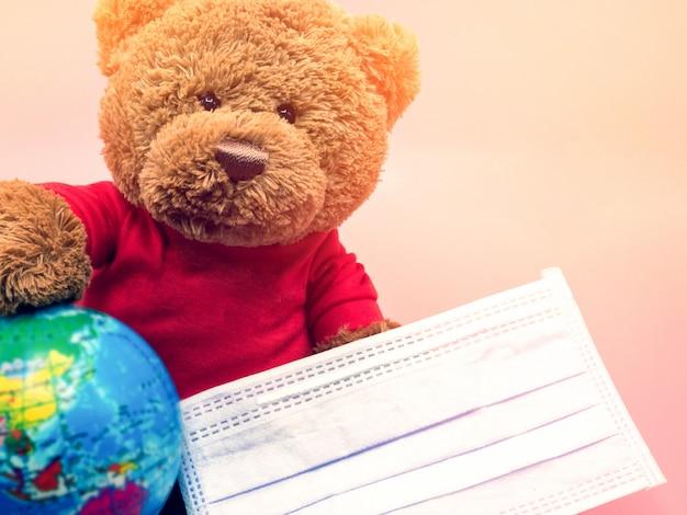 Urso de pelúcia marrom com máscara cirúrgica proteger contra coronavírus e poeira pm2.5 em fundo rosa. conceito de higiene e saúde