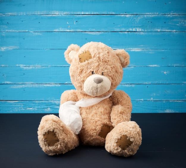 Urso de pelúcia marrom com pata de bandagem branca rebobinada
