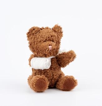 Urso de pelúcia marrom com pata de bandagem rebobinado branco sobre um fundo branco