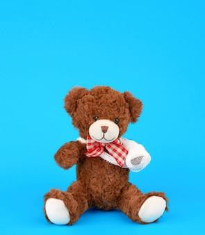 Urso de pelúcia marrom com rebobinado pata de bandagem branca sobre um fundo azul