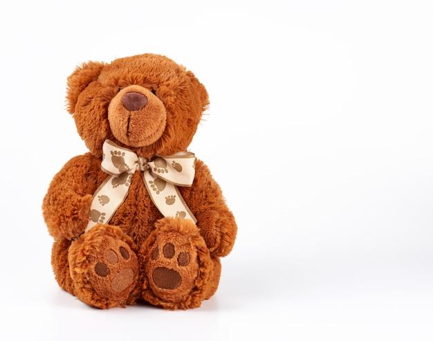 Urso de pelúcia marrom com um laço no pescoço