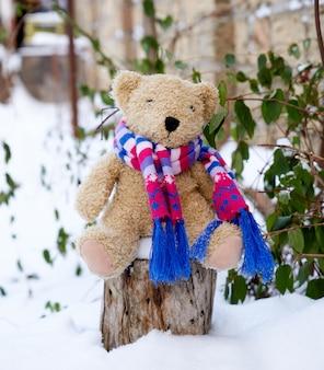 Urso de pelúcia marrom crianças em um cachecol de malha brilhante, sentado no tronco