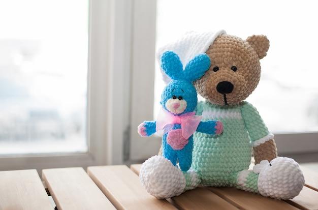 Urso de pelúcia marrom de bicho de pelúcia e pequeno coelho azul de malha na madeira. copie o espaço.