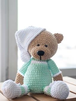 Urso de pelúcia marrom de bicho de pelúcia em roupas lilás e chapéu branco na madeira.