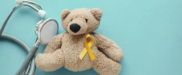 Urso de pelúcia marrom de crianças com fita de ouro amarelo e estetoscópio