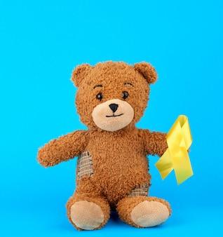 Urso de pelúcia marrom senta-se e tem na pata uma fita de seda amarela sobre um fundo azul