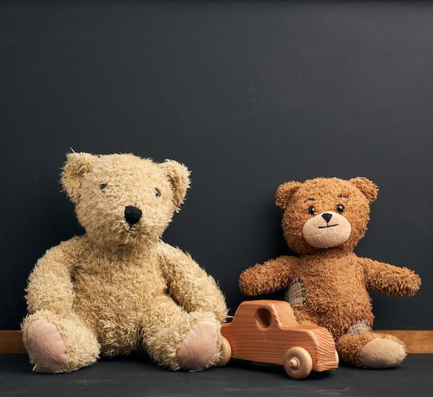 Urso de pelúcia marrom senta-se em uma mesa de madeira marrom