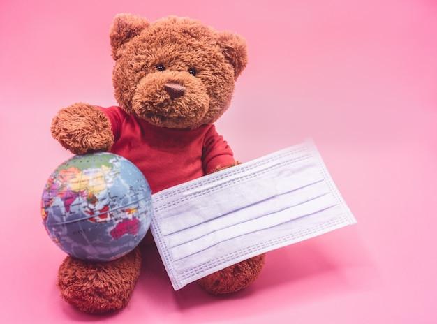Urso de pelúcia marrom usando máscara segurando o globo da terra, apoiando o distanciamento social e trabalhando em casa para reduzir a disseminação do coronavírus. covid-19, coronavírus, conceito de distanciamento social.