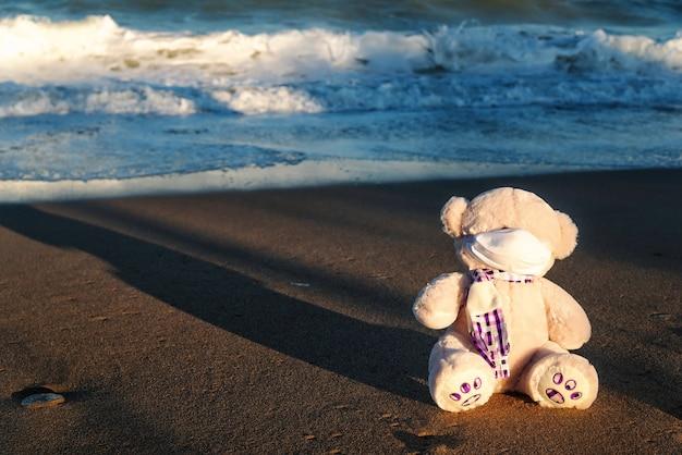 Urso de pelúcia mascarado à beira-mar, conceito viral