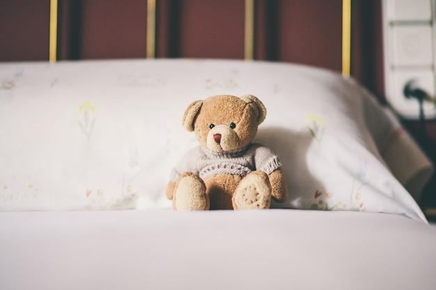 Urso de pelúcia na cama, espaço para texto.