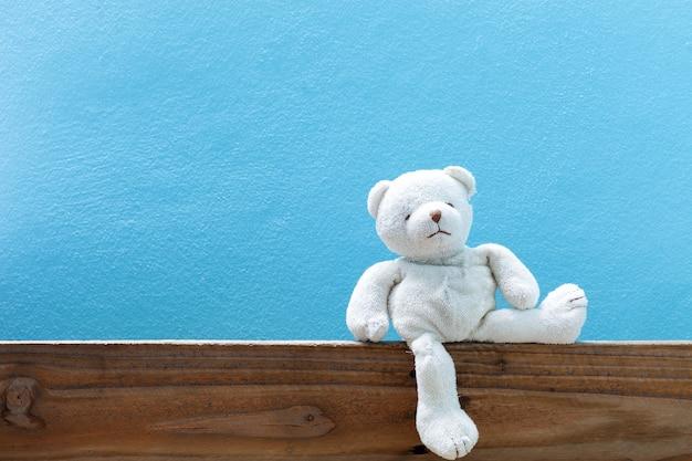 Urso de pelúcia na madeira velha no fundo da parede azul da frente