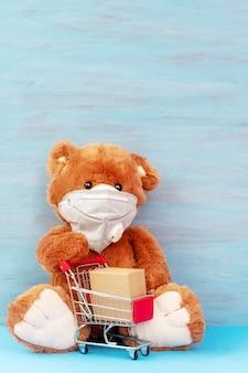 Urso de pelúcia na máscara com carrinho de compras. caixas sem contato para entrega. compras on-line e entrega expressa.