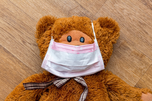 Urso de pelúcia na máscara protetora médica