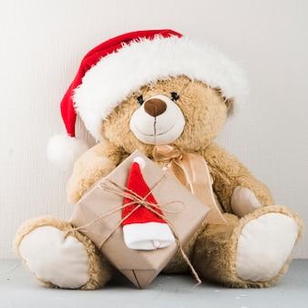 Urso de pelúcia no chapéu de papai noel com presente