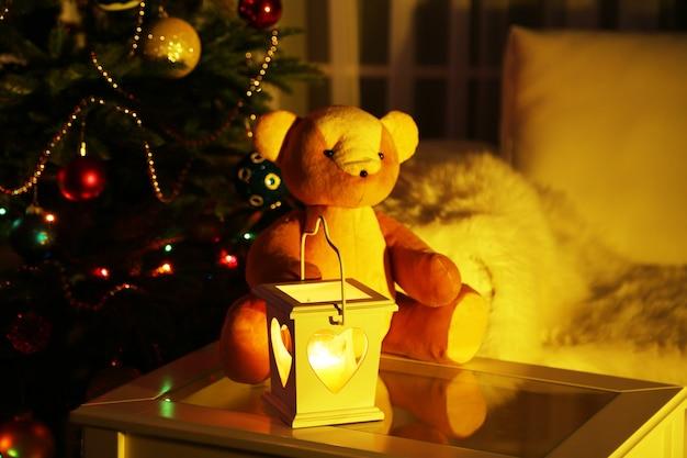 Urso de pelúcia no interior da casa no fundo da árvore de natal decorada