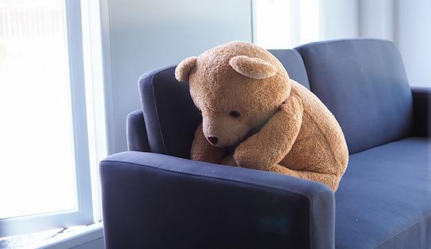 Urso de pelúcia sentado encostado no sofá sozinho
