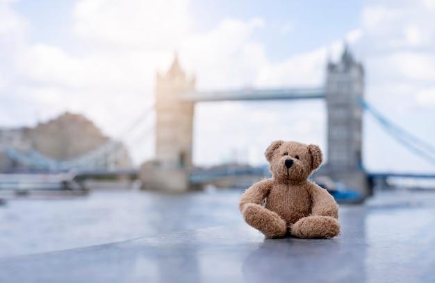 Urso de pelúcia sentado sozinho com o fundo desfocado de ponte de torre de londres