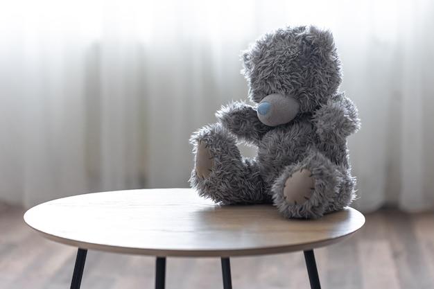 Urso de pelúcia solitário em um fundo desfocado no interior do espaço da cópia da sala.