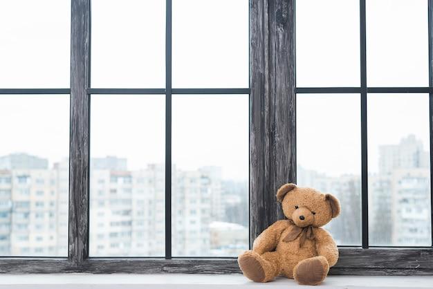Urso de pelúcia solitário sentado perto do peitoril da janela fechada