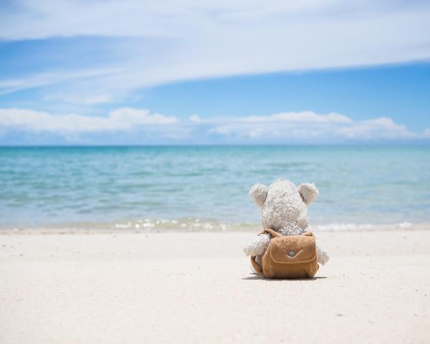 Urso de pelúcia sozinho sentado na praia de areia com borrão do mar azul e céu azul. conceito de coração partido.