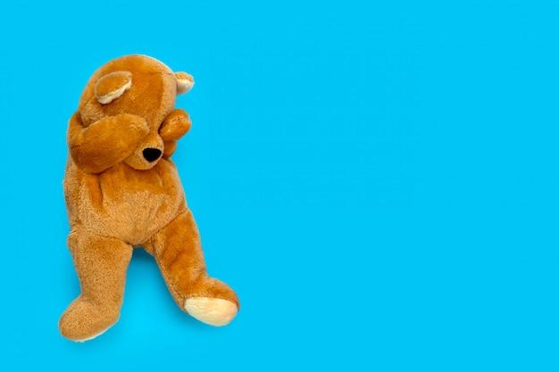 Urso de pelúcia triste solitário sobre fundo azul.