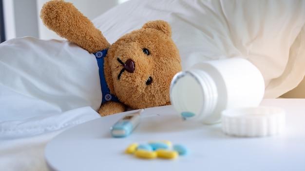 Urso de pelúcia triste teve uma dor de cabeça e febre, deitado doente na cama