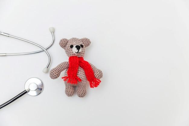 Urso do brinquedo do projeto simplesmente mínimo e estetoscópio do equipamento da medicina isolado na superfície branca. cuidados de saúde crianças médico conceito. símbolo pediatra. vista plana, cópia superior vista espaço